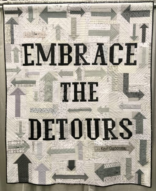 """Embrace the Detours"" by Washington DC Modern Quilt Guild @dcmqg Statement: ""Embrace the Detours was conjured by a small group within DCMQG who jumped from the challenge description to brainstorming about words for the quilt. We settled on Kevin Charbonneau's iconic admonition to Embrace the Detours! Over 30 DCMQG members created the arrows and letters of the quilt. The next step was the incredible ruler quilting by Sarah Thomas @sariditty . Thanks to all DCMQG members for this impressive group effort."" Modern quilt featured in the Charity Quilts category at QuiltCon 2020 in Austin, Texas presented by the Modern Quilt Guild."