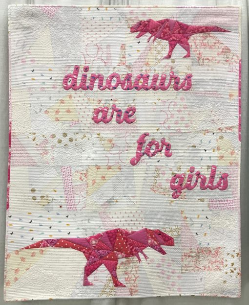 """""""I Can't Believe I Have to Say This"""" by Sylvia Schaefer @flyingparrotquilts Statement: """" 'it's hard to find fabrics for boys, so we have new dinosaur fabric.' 'You must have sons, wearing a dinosaur skirt like that!' 'Ill just tell her that dinosaurs are for boys.' These sorts of comments finally boiled over into this quilt. Paper pieced dinosaurs and letters were combined with improv piecing. I tried to chose """"girly"""" fabrics, colors, and other elements to contrast with the perceived masculinity of the T. Rexes."""" Modern quilt featured in the Piecing category at QuiltCon 2020 in Austin, Texas presented by the Modern Quilt Guild."""
