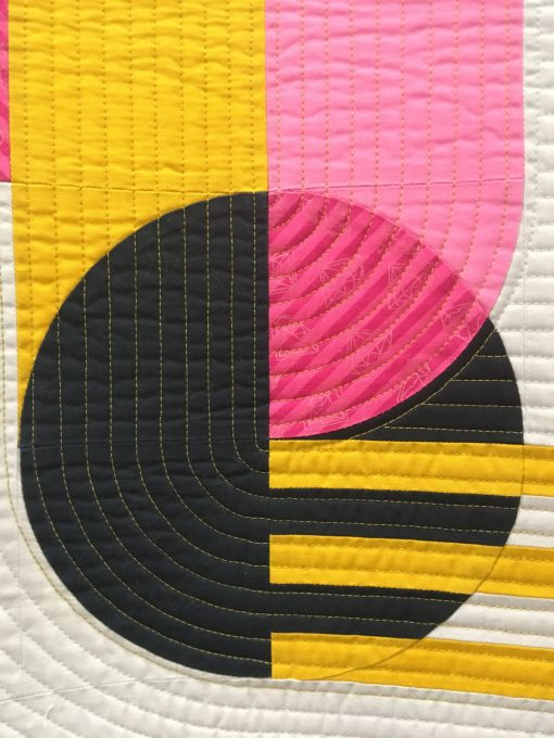 "detail of ""Bubble Gum"" by Sophie Zaugg @lunalovequilts Awarded 2nd place in Use of Negative Space category Statement: ""The design was inspired by a geometric street art mural. I included the main motif in negative space to showcase it and mimic the concrete wall of the original work. I placed the yellow strips as if they linked the motif to the edge of the quilt. All the curves are hand appliquéd."" Modern quilt featured in the Use of Negative Space category at QuiltCon 2020 in Austin, Texas presented by the Modern Quilt Guild."