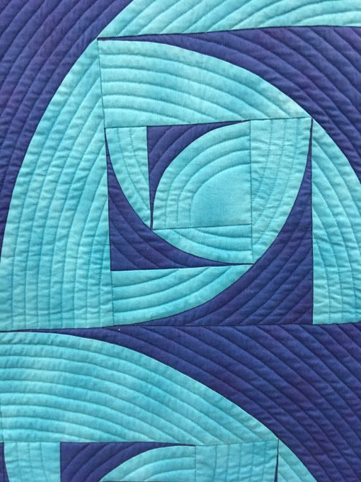 """detail of """"Breakers"""" by Pat Forster Statement: """"The block is my original design—a fractal based on the Drunkard's Path block. Contrasting blues, the block that evokes water in turmoil, the block arrangement that shows breakers rolling to shore, the quilt title, and the manta ray backing fabric, all complement each other. Machine pieced and quilted."""" Modern quilt featured in the Piecing category at QuiltCon 2020 in Austin, Texas presented by the Modern Quilt Guild."""