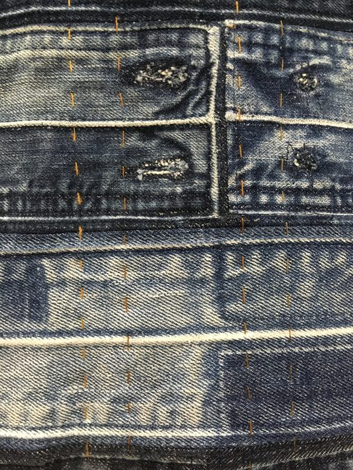 """detail of """"Waist Not"""" by Eliu Hernandez @madeorremade Statement: """"Waist Not, not only a play on words, but also a play in practice. Denim waistbands, batting and backing have been reclaimed. The thread has also been reclaimed from jeans. The hand-quilting highlights the harvested thread. Textile waste is a huge contributors to landfills—Waist Not shows that there is beauty and fiction in what many consider trash."""" Modern quilt featured in the Quilting Challenge category at QuiltCon 2020 in Austin, Texas presented by the Modern Quilt Guild."""