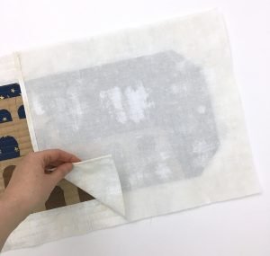 Layering fabric and quilt block to make an envelope pillow.